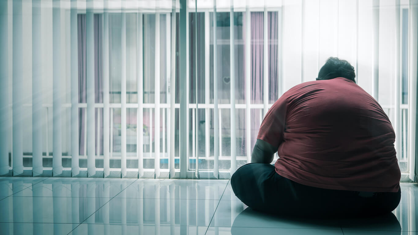 overweight individual sitting on floor - solemnly