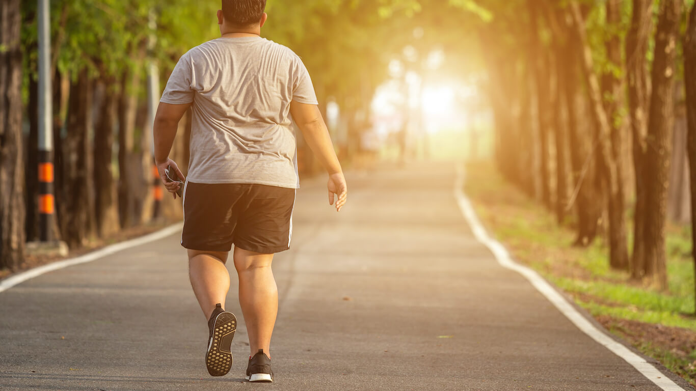 man working out outdoors walking on trail